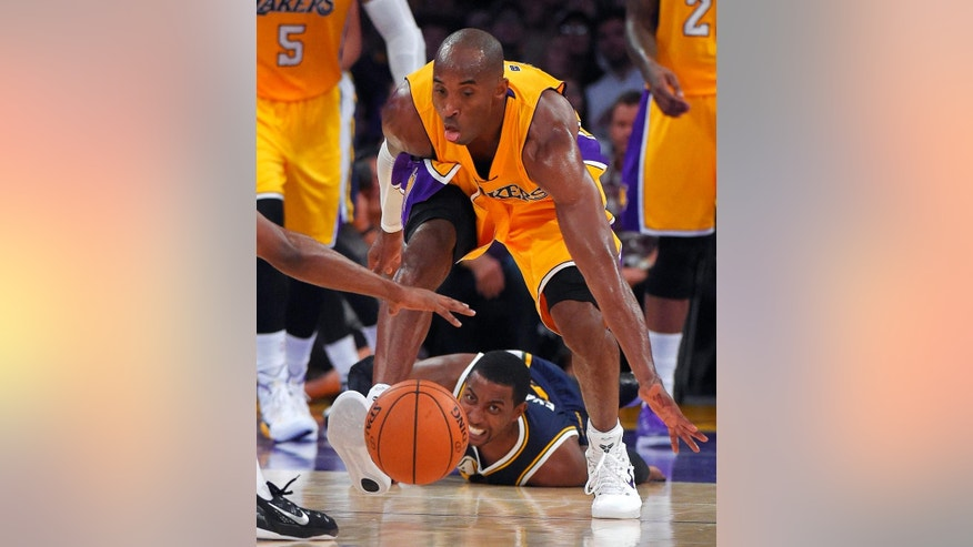Los Angeles Lakers guard Kobe Bryant, top, picks up a ball that was lost by Utah Jazz forward Jeremy Evans, below, during the first half of a preseason NBA basketball game, Sunday, Oct. 19, 2014, in Los Angeles. (AP Photo/Mark J. Terrill)
