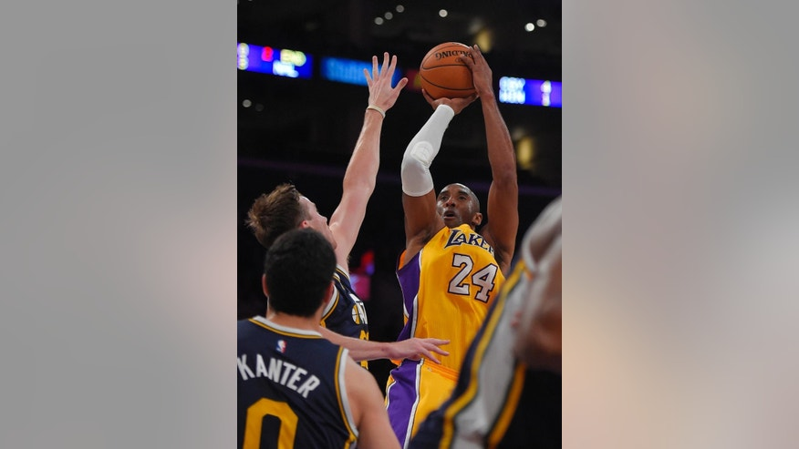 Los Angeles Lakers guard Kobe Bryant puts up a shot as Utah Jazz guard Gordon Hayward, second from left, and center Enes Kanter, of Turkey, defend during the first half of a preseason NBA basketball game, Sunday, Oct. 19, 2014, in Los Angeles. (AP Photo/Mark J. Terrill)