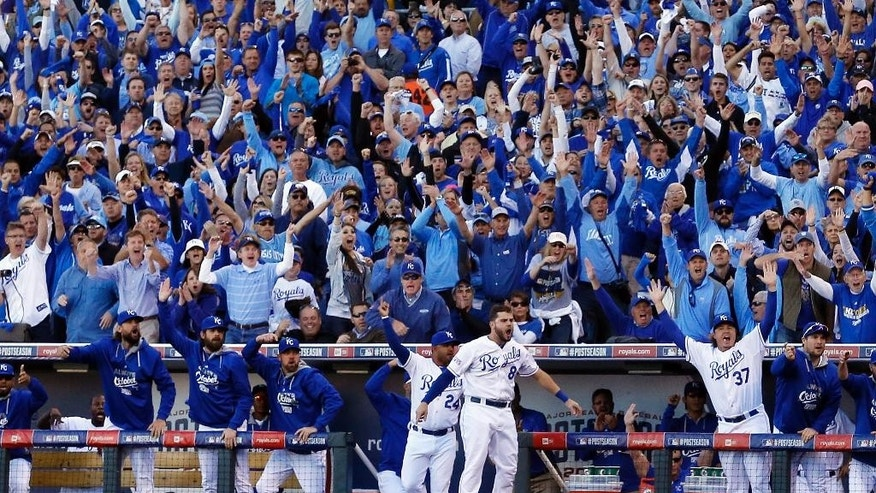 FILE - In this Oct. 15, 2014, file photo, Kansas City Royals players and fans celebrate after Alcides Escobar scores during the first inning of Game 4 of the American League baseball championship series against the Baltimore Orioles in Kansas City, Mo. Kansas City fans have come a long, long way from spring training when many hated the young team without a lot of star appeal. The city is now caught up in a love affair with the Royals, and the players are reciprocating, reminding many folks of a bygone era in professional sports.  (AP Photo/Matt Slocum, File)