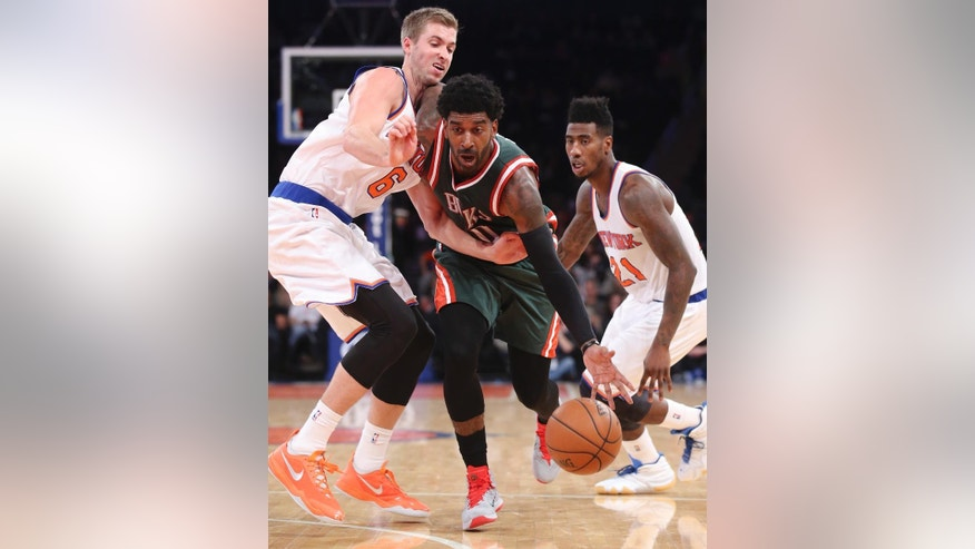 Milwaukee Bucks guard O.J. Mayo (00) drives through New York Knicks forward Travis Wear (6) and guard Iman Shumpert (21) in the second half of their preseason NBA basketball game at Madison Square Garden, Monday, Oct. 20, 2014, in New York. The Bucks won, 120-107. (AP Photo/John Minchillo)