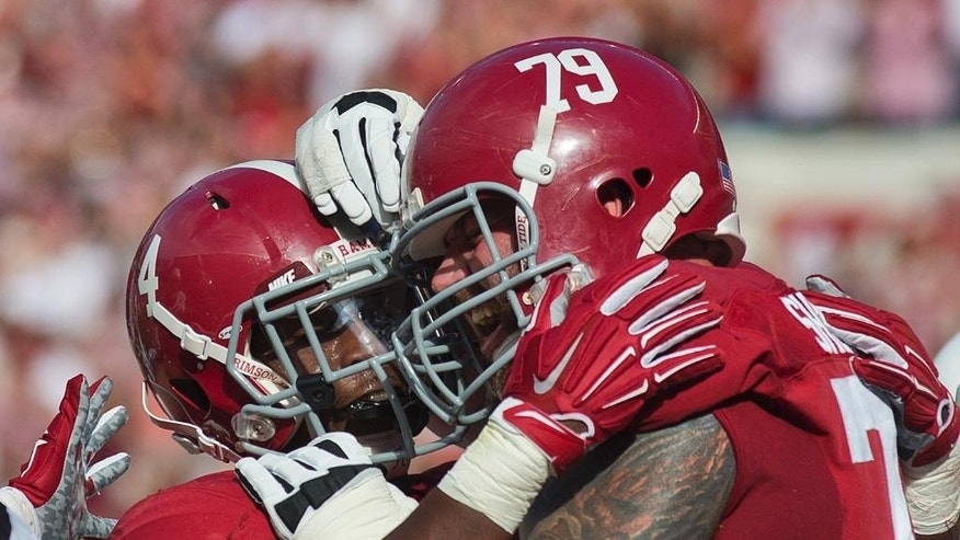 Alabama running back T.J. Yeldon (4) and offensive lineman Austin Shepherd (79) celebrate after Yeldon scored a touchdown against Texas A&M during the first half of an NCAA college football game on Saturday, Oct, 18, 2014, in Tuscaloosa, Ala. (AP Photo/Brynn Anderson)
