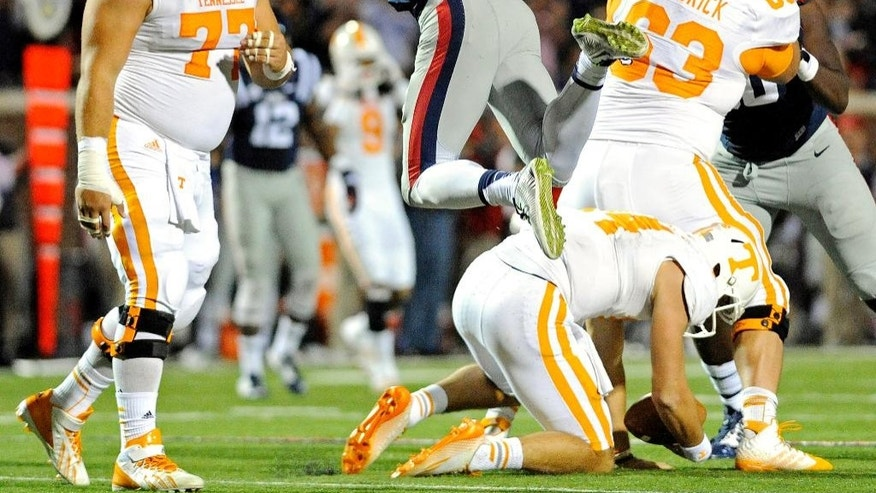 Mississippi defensive end Marquis Haynes (27) reacts after sacking Tennessee quarterback Justin Worley, lower right, during the second half of an NCAA college football game in Oxford, Miss., Saturday, Oct. 18, 2014. No. 3 Mississippi won 34-3. (AP Photo/The Daily Mississippian, Thomas Graning)