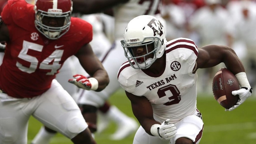 Texas A&M running back Trey Williams (3) carries the ball as Alabama defensive lineman Dalvin Tomlinson (54) pursues during the second half of an NCAA college football game on Saturday, Oct. 18, 2014, in Tuscaloosa, Ala. (AP Photo/Butch Dill)