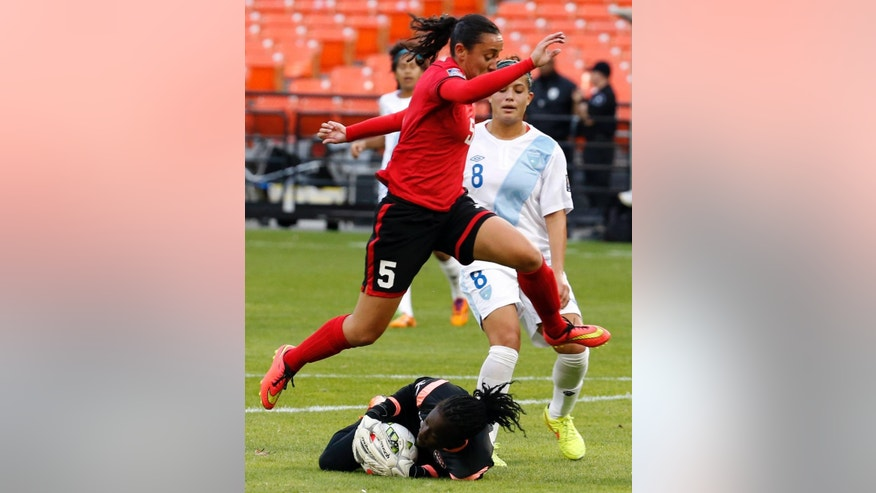 Trinidad & Tobago defender Arin King (5) jumps over goalkeeper Tenesah Palmer who holds onto the ball with Guatemala forward Maria Monterroso (8) nearby, during the first half of a CONCACAF soccer match, at RFK Stadium, Monday, Oct. 20, 2014, in Washington. (AP Photo/Alex Brandon)