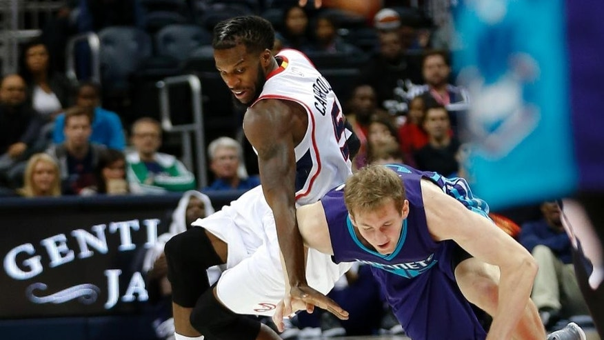 Charlotte Hornets center Cody Zeller , right, recovers the ball after it was knocked away by Atlanta Hawks forward DeMarre Carroll (5) during the second half of an NBA pre-season basketball game Monday, Oct. 20, 2014, in Atlanta. Atlanta won 117-114 in overtime. (AP Photo/John Bazemore)