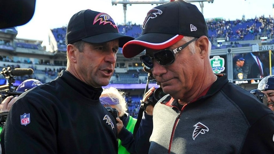 Baltimore Ravens head coach John Harbaugh, left, speaks with Atlanta Falcons head coach Mike Smith after an NFL football game, Sunday, Oct. 19, 2014, in Baltimore. Baltimore won 29-7. (AP Photo/Gail Burton)