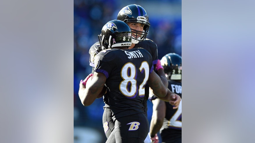 Baltimore Ravens quarterback Joe Flacco, right, celebrates with wide receiver Torrey Smith after Smith scored a touchdown in the second half of an NFL football game against the Atlanta Falcons, Sunday, Oct. 19, 2014, in Baltimore. Baltimore won 29-7. (AP Photo/Nick Wass)