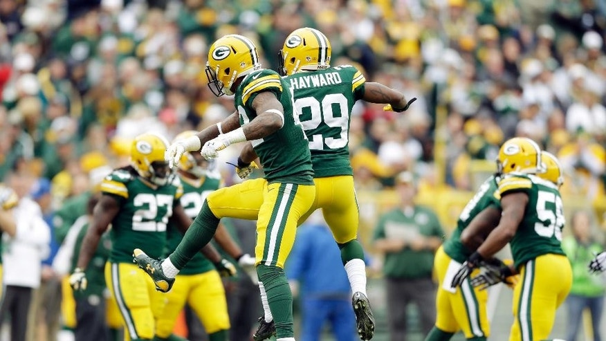 Green Bay Packers' Casey Hayward (29) and Morgan Burnett celebrate a fourth and short stop during the second half of an NFL football game against the Carolina Panthers Sunday, Oct. 19, 2014, in Green Bay, Wis. (AP Photo/Tom Lynn)