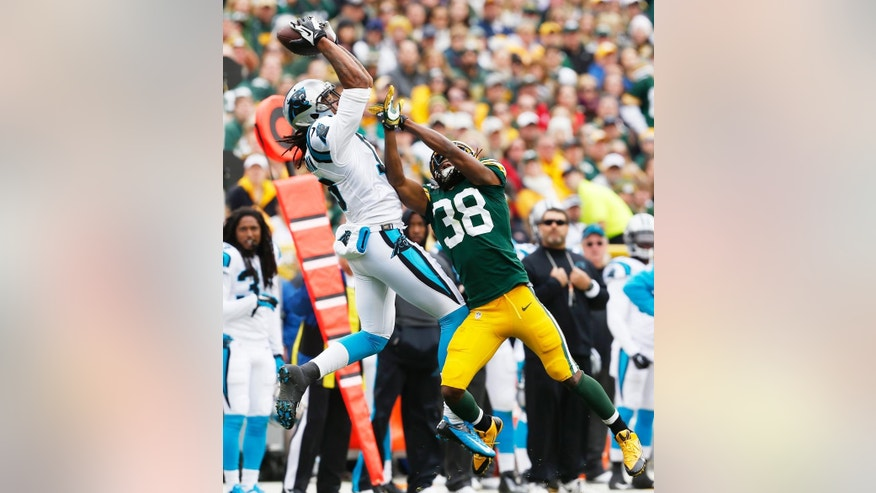 Carolina Panthers' Kelvin Benjamin goes up for a pass against Green Bay Packers' Tramon Williams (38) during the first half of an NFL football game Sunday, Oct. 19, 2014, in Green Bay, Wis. (AP Photo/Mike Roemer)