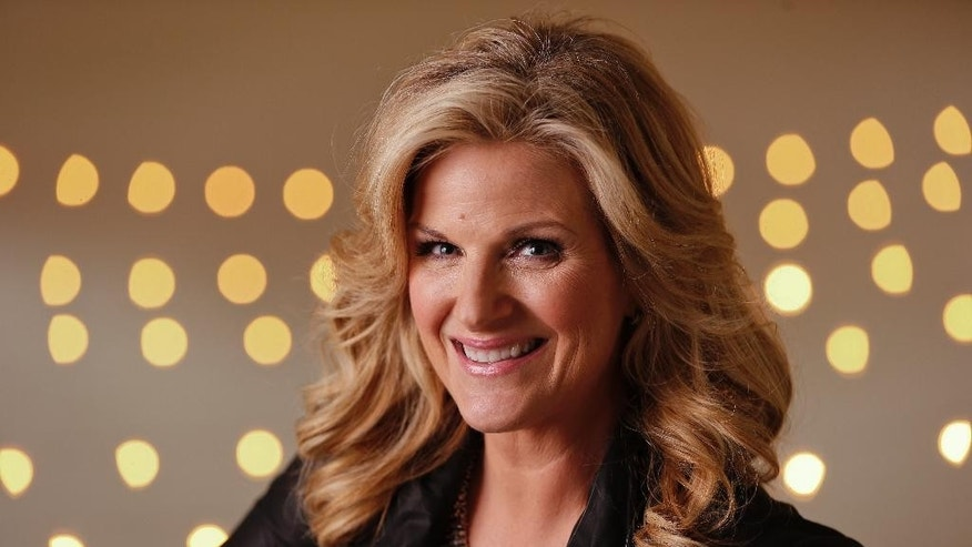 "FILE - In this Aug. 18, 2014 file photo, Trisha Yearwood poses in Nashville, Tenn.  Yearwood and Carlos Santana are among the musicians set to perform the national anthem during the World Series. Major League Baseball said Monday, Oct. 20, that Yearwood will sing ""The Star Spangled Banner"" ahead of Game 1 when the San Francisco Giants play the Kansas City Royals on Tuesday, Oct. 22, at Kauffman Stadium in Kansas City, Mo. (AP Photo/Mark Humphrey, File)"