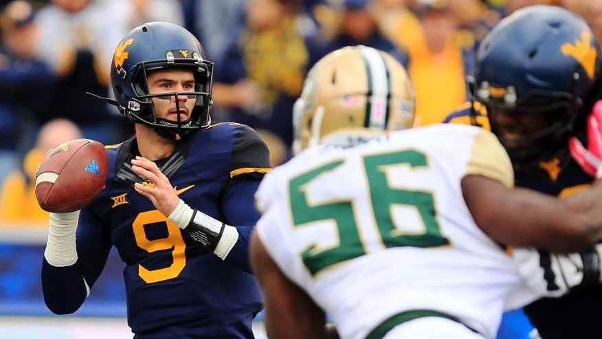 West Virginia quarterback Clint Trickett (9) looks for a receiver during the first quarter of an NCAA college football game against Baylor in Morgantown, W.Va., Saturday, Oct. 18, 2014. West Virginia won 41-27. (AP Photo/Chris Jackson)