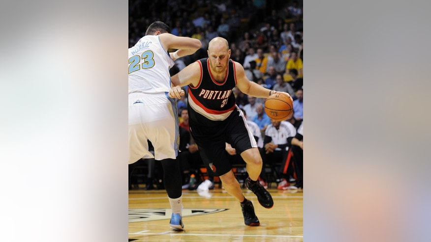 Portland Trail Blazers center Chris Kaman, right, dribbles past Denver Nuggets forward Jusuf Nurkic during the first half of an NBA preseason basketball game in Boulder, Colo., on Tuesday, Oct. 21, 2014. (AP Photo/Chris Schneider)