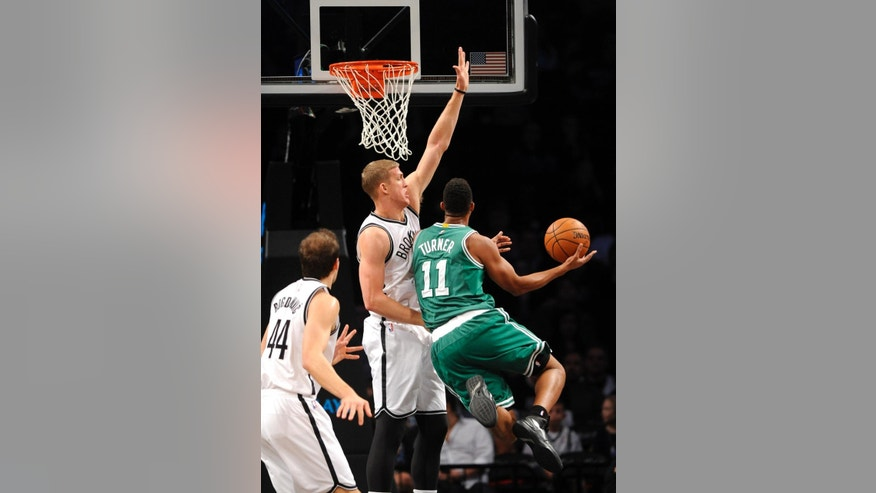 Brooklyn Nets forward Mason Plumlee (1) blocks a shot by Boston Celtics guard Evan Turner (11) as Nets forward Bojan Bogdanovic (44) defends from behind  during the first half of a preseason NBA basketball game on Sunday, Oct. 19, 2014 at Barclays Center in New York. (AP Photo/Kathy Kmonicek)
