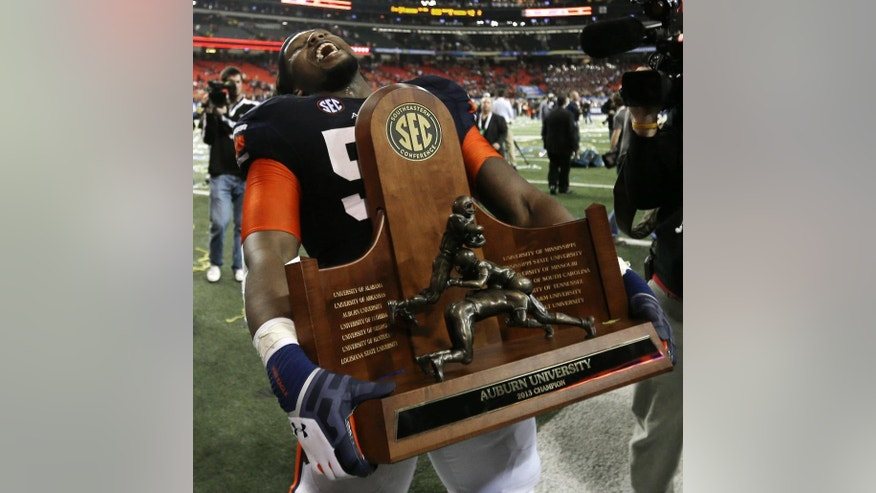FILE - In this Dec. 7, 2013, file photo, Auburn offensive linesman Avery Young (56) carries the championship trophy defeating Missouri 59-42 in the Southeastern Conference NCAA college football championship game in Atlanta. Its fans were gloating about being the first conference to place four of the top five teams in the AP Top 25. Those who have had it up to here with the all the SEC love had a different take: #SECBias. (AP Photo/David Goldman, File)