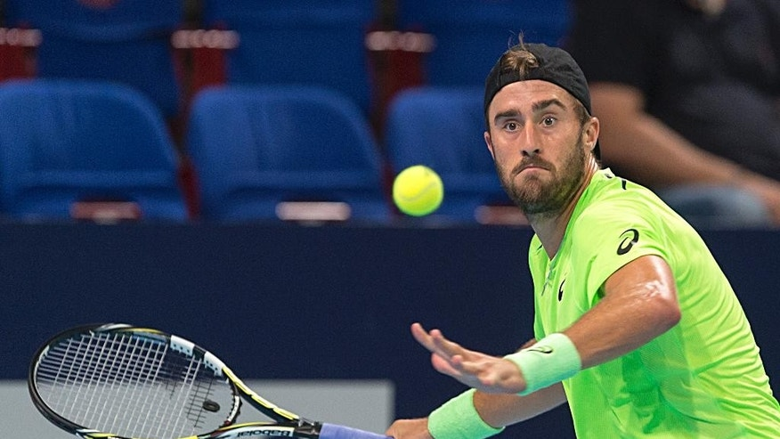 US tennis player Steve Johnson  returns a ball to Canada's Milos Raonic during their first round match at the Swiss Indoors tennis tournament at the St. Jakobshalle in Basel, Switzerland, on Tuesday, Oct. 21, 2014.   (AP Photo/Keystone,Georgios Kefalas)