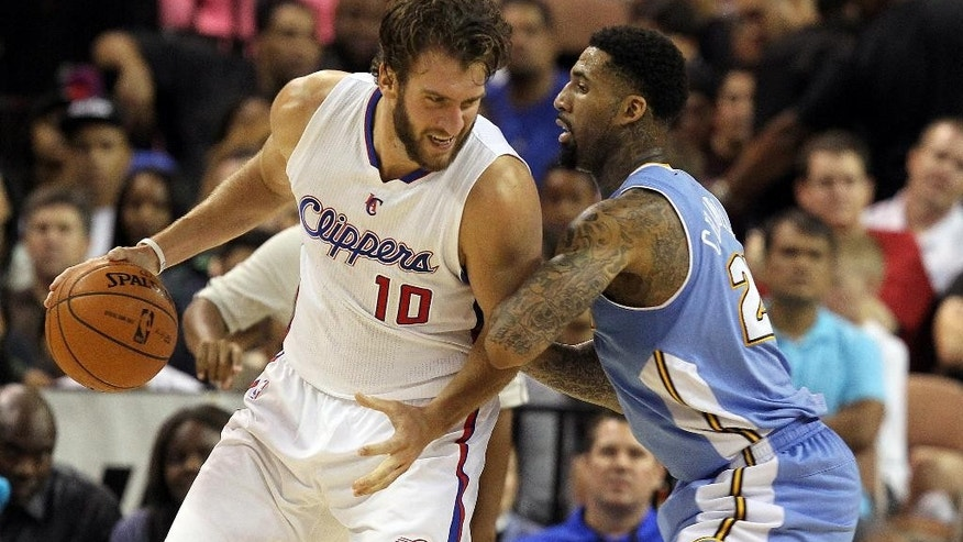 Los Angeles Clippers forward Spencer Hawes (10) drives covered by Denver Nuggets forward Wilson Chandler (21) during the second half of an NBA preseason basketball game on Saturday, Oct. 18, 2014, in Las Vegas. The Nuggets defeated the Clippers 104-93. (AP Photo/Isaac Brekken)