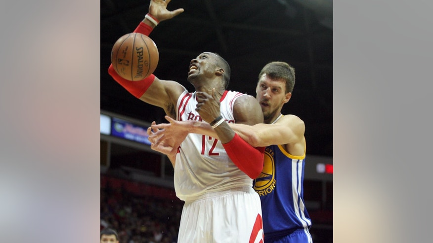 Houston Rockets Dwight Howard, left, gets fouled by Golden State Warriors defender David Lee during the first half of an NBA preseason basketball game in Hidalgo, Texas, Sunday, Oct. 19, 2014. (AP Photo/Delcia Lopez)