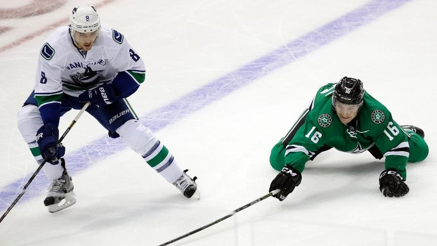 Vancouver Canucks' Chris Tanev (8) has the puck stripped away by Dallas Stars' Ryan Garbutt (16) during the third period of an NHL hockey game, Tuesday, Oct. 21, 2014, in Dallas. The Stars won 6-3. (AP Photo/Tony Gutierrez)