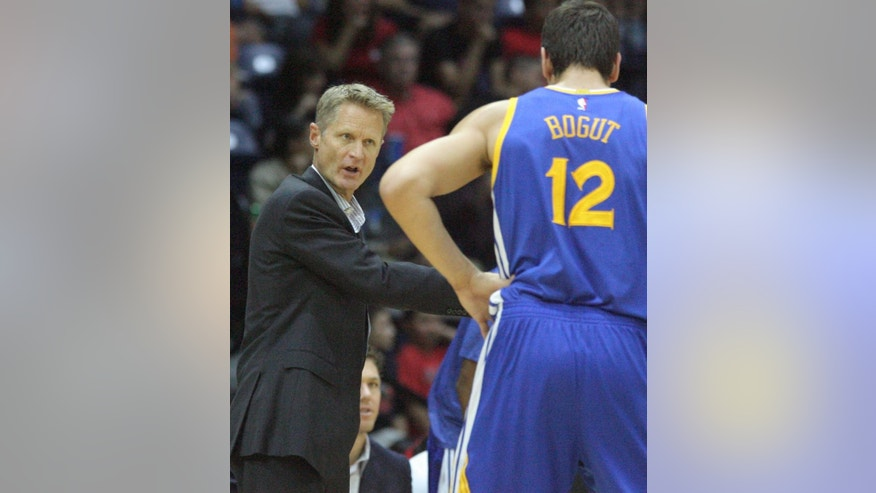 Golden State Warriors coach Steve Kerr, left, instructs Andrew Bogut during the second half of an NBA preseason basketball game in Hidalgo, Texas, Sunday, Oct. 19, 2014. (AP Photo/Delcia Lopez)