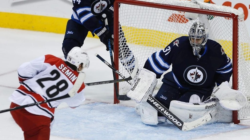 Carolina Hurricanes' Alexander Semin (28) has a shot stopped by Winnipeg Jets goaltender Ondrej Pavelec (31) as Jets' Zach Bogosian watches during the third period of an NHL hockey game Tuesday, Oct. 21, 2014, in Winnipeg, Manitoba. (AP Photo/The Canadian Press, John Woods)