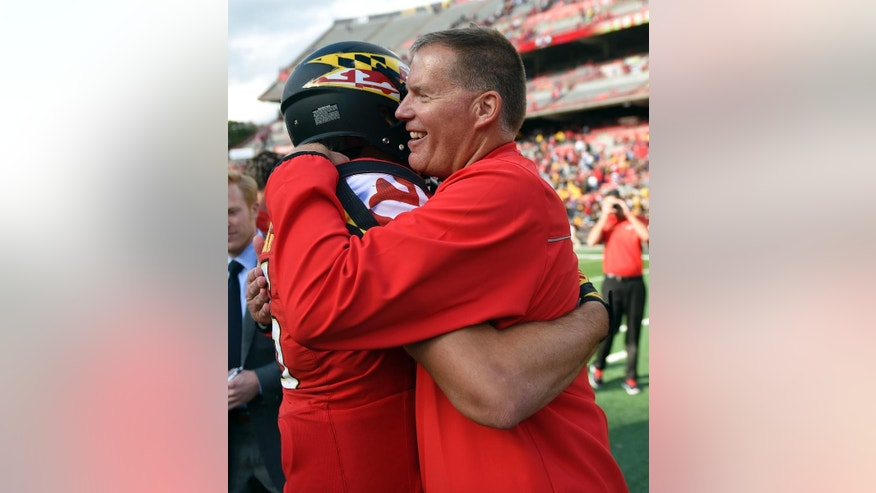Maryland head coach Randy Edsall, right, hugs quarterback C.J. Brown after they defeated Iowa 38-31 in an NCAA college football game, Saturday, Oct. 18, 2014, in College Park, Md. (AP Photo/Nick Wass)