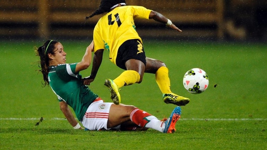 Mexico's Bianca Sierra, bottom, slides under Jamaica's Donna-Kay Henry (4) during the first half of a CONCACAF soccer match at RFK Stadium, Tuesday, Oct. 21, 2014, in Washington. (AP Photo/Nick Wass)