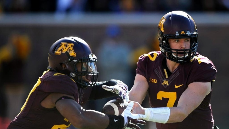 Minnesota quarterback Mitch Leidner (7) hands off the ball to running back David Cobb (27) during the second half of an NCAA college football game against Purdue, Saturday, Oct. 18, 2014, in Minneapolis. Minnesota won 39-38. (AP Photo/Hannah Foslien)