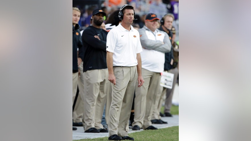 Oklahoma State coach Mike Gundy watches play late in the second half of an NCAA college football game against TCU, Saturday, Oct. 18, 2014, in Fort Worth, Texas. TCU won 42-9. (AP Photo/Tony Gutierrez)