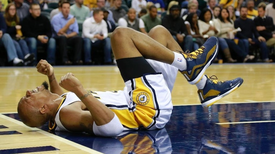 Indiana Pacers forward David West reacts in pain after falling during a play against the Dallas Mavericks in the second half of a preseason NBA basketball game in Indianapolis, Saturday, Oct. 18, 2014. Indiana won 98-93.  (AP Photo/R Brent Smith)