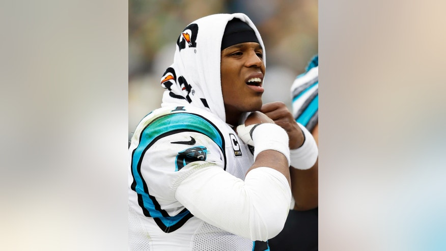 Carolina Panthers' Cam Newton puts a towel on his head during the second half of an NFL football game against the Green Bay Packers Sunday, Oct. 19, 2014, in Green Bay, Wis. (AP Photo/Tom Lynn)