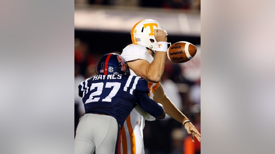 Mississippi defensive end Marquis Haynes (27) jars the ball loose from Tennessee quarterback Justin Worley (14) in the second half of an NCAA college football game in Oxford, Miss., Saturday, Oct. 18, 2014. No. 3 Mississippi won 34-3. (AP Photo/Rogelio V. Solis)