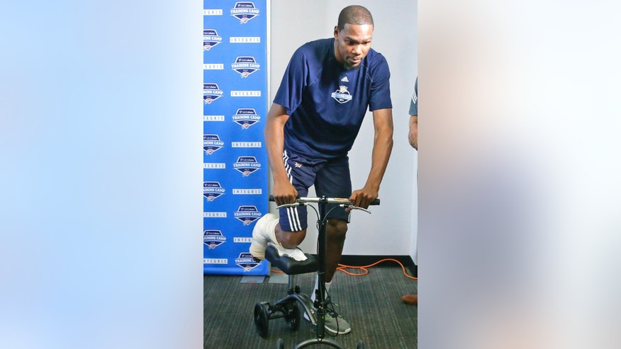 Oklahoma City Thunder forward Kevin Durant leaves a news conference with his right leg balanced on a scooter, in Oklahoma City, Tuesday, Oct. 21, 2014. Durant said he's been antsy since finding out he will miss the early part of the season with a Jones fracture in his right foot. The reigning NBA MVP spoke to the media Tuesday morning for the first time since the injury. (AP Photo/Sue Ogrocki)
