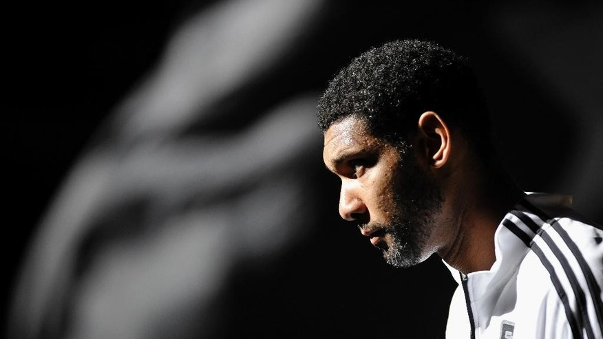 San Antonio Spurs forward Tim Duncan takes the court before a preseason NBA basketball game against the Miami Heat, Saturday, Oct. 18, 2014, in San Antonio. (AP Photo/Darren Abate)