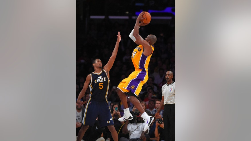 Los Angeles Lakers guard Kobe Bryant, right, puts up a shot as Utah Jazz guard Rodney Hood defends during the second half of a preseason NBA basketball game, Sunday, Oct. 19, 2014, in Los Angeles.  The Lakers on 98-91. (AP Photo/Mark J. Terrill)