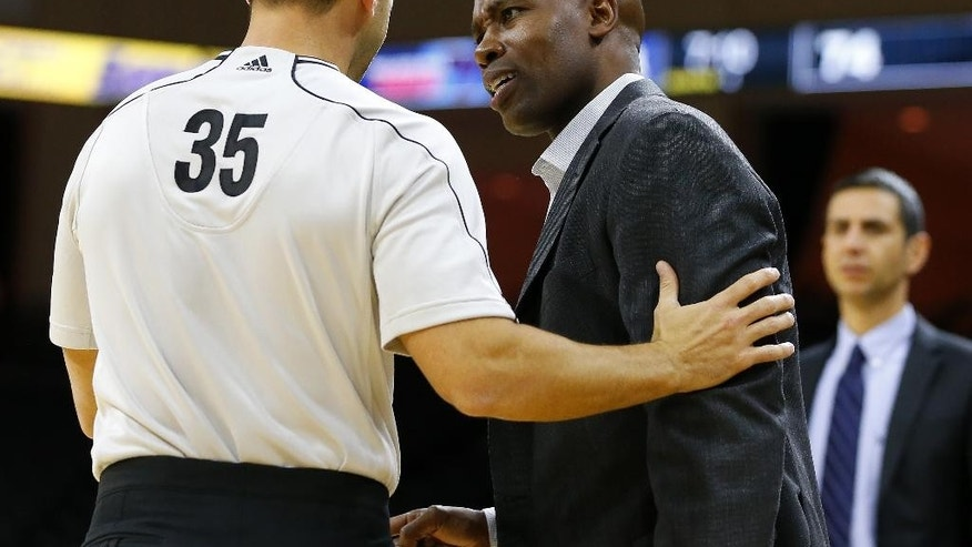 Orlando Magic's head coach: Jacque Vaughn talks with referee Kane Fitzgerald (35) during a timeout against the Philadelphia 76ers' during the second half of an NBA pre-season basketball game in Allentown, Pa., Saturday, Oct. 18, 2014. The 76ers defeated the Magic 95-84. (AP Photo/Rich Schultz)