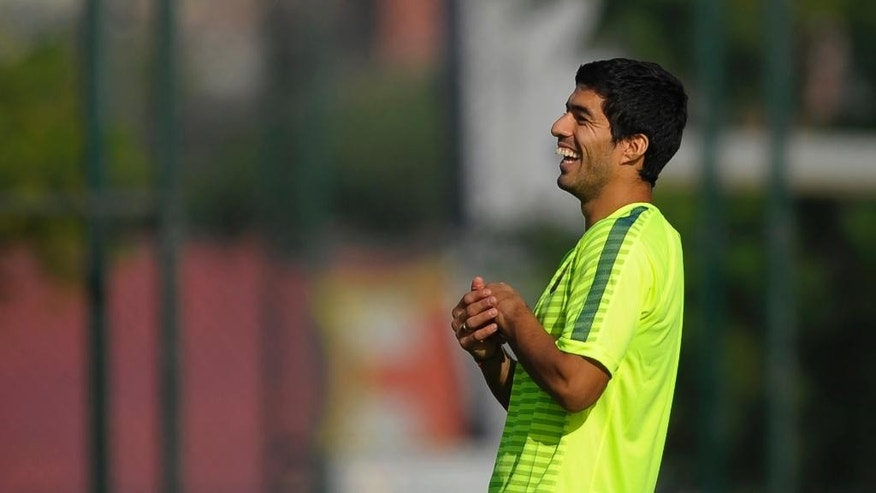 FC Barcelona's Luis Suarez, from Uruguay, laughs during a training session at the Sports Center FC Barcelona Joan Gamper in San Joan Despi, Spain, Monday, Oct. 20, 2014. FC Barcelona will play against Ajax in a group F Champions League on Tuesday Oct. 21. (AP Photo/Manu Fernandez)