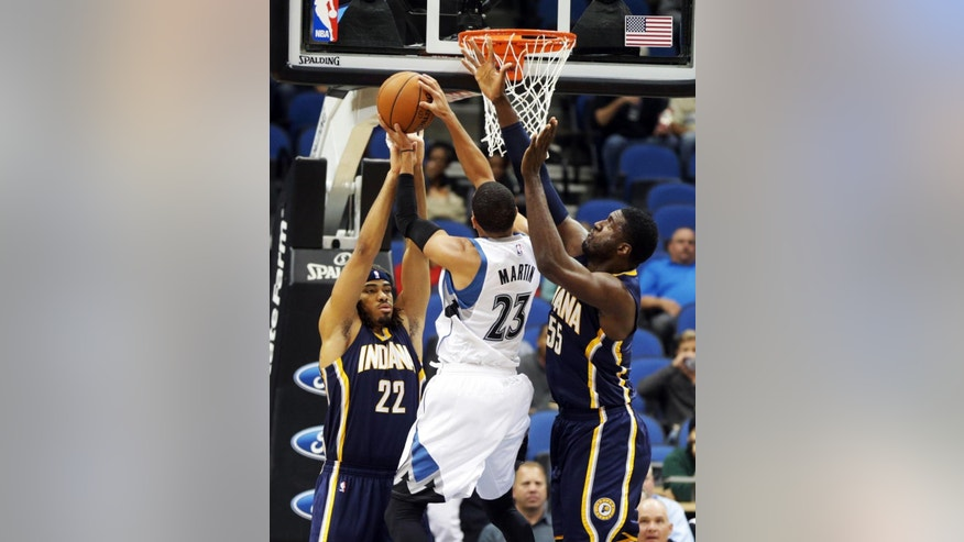 Indiana Pacers' Chris Copeland, left, and Roy Hibbert, right, try to break up a shot attempt by Minnesota Timberwolves' Kevin Martin in the first quarter of a preseason NBA basketball game, Tuesday, Oct. 21, 2014, in Minneapolis. (AP Photo/Jim Mone)