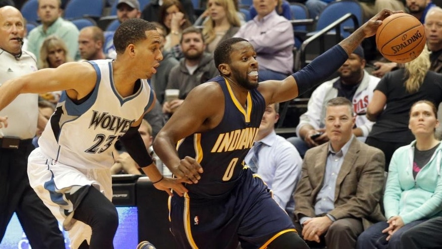 Indiana Pacers' C.J. Miles, right, reaches for control of the ball as he drives, pursued by Minnesota Timberwolves' Kevin Martin in the first quarter of a preseason NBA basketball game, Tuesday, Oct. 21, 2014, in Minneapolis. (AP Photo/Jim Mone)