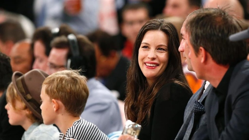 Actress Liv Tyler laughs  from her courtside seat during the first half of an NBA basketball game between the Washington Wizards and the New York Knicks at Madison Square Garden in New York, Wednesday, Oct. 22, 2014. (AP Photo/Kathy Willens)