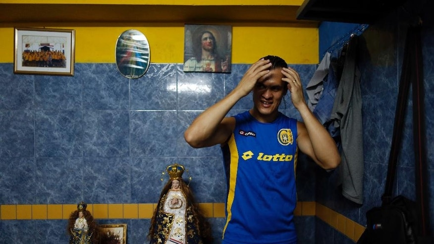 In this Oct. 18, 2014 photo, Deportivo Capiata player Arturo Aquino gels his hair after practice inside the team's dressing room where a small altar of the Virgin of Caacupe stands in Capiata, Paraguay. After Capiata defeated Argentina's Boca Juniors in a first leg of the Copa Sudamericana, the team must face the Argentine juggernaut again on Thursday, Oct. 23 for the second leg. The winner goes to the quarterfinals. (AP Photo/Jorge Saenz)
