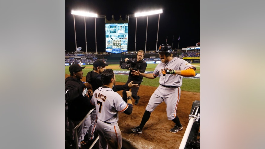 San Francisco Giants Hunter Pence, right, is congratulated by his teammates after hitting a two-run home run during the first inning of Game 1 of baseball's World Series Tuesday, Oct. 21, 2014, in Kansas City, Mo. (AP Photo/Matt Slocum )