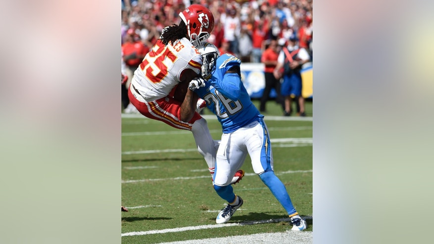 Kansas City Chiefs running back Jamaal Charles (25) is upended by San Diego Chargers cornerback Brandon Flowers while scoring a touchdown during the first half of an NFL football game Sunday, Oct. 19, 2014, in San Diego. (AP Photo/Denis Poroy)