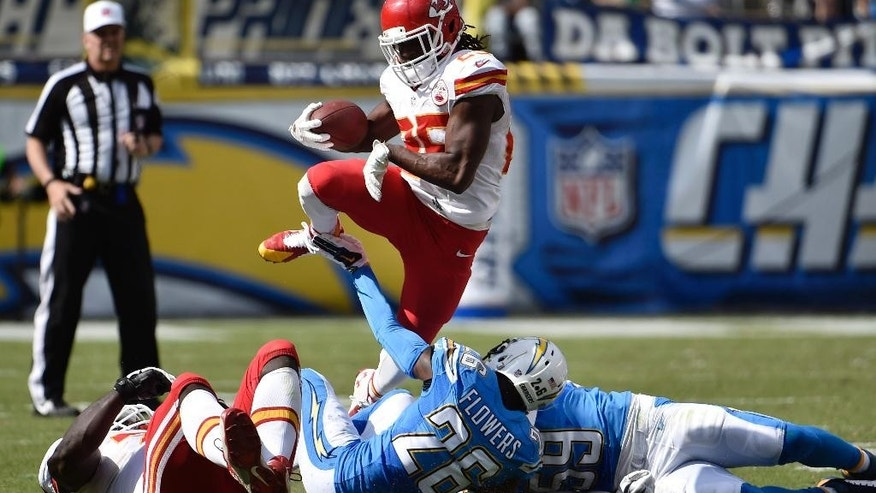 Kansas City Chiefs running back Jamaal Charles, top, leaps over San Diego Chargers cornerback Brandon Flowers (26) and inside linebacker Andrew Gachkar, right, during the first half of an NFL football game Sunday, Oct. 19, 2014, in San Diego. (AP Photo/Denis Poroy)