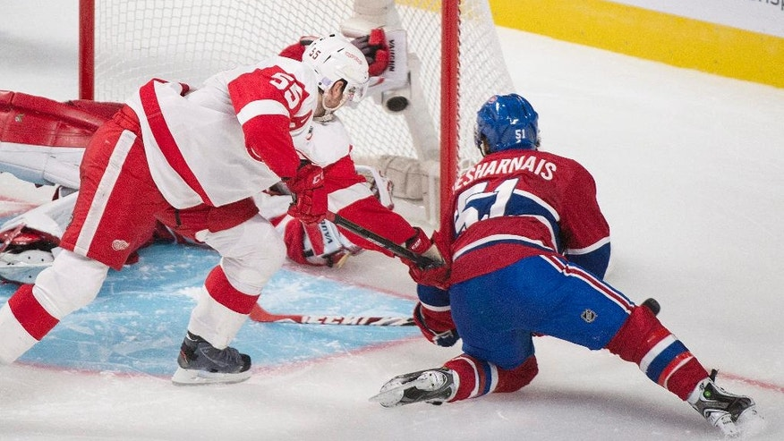 Montreal Canadiens' David Desharnais (51) scores against Detroit Red Wings goaltender Jimmy Howard, left, as Red Wings' Niklas Kronwall (55) defends during overtime period NHL hockey action in Montreal, Tuesday, Oct. 21, 2014. (AP Photo/The Canadian Press, Graham Hughes)