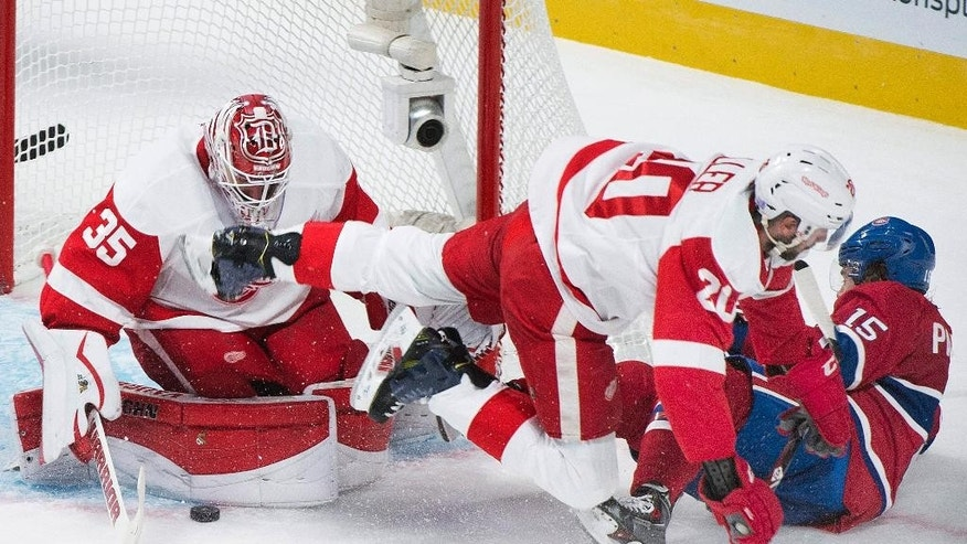 CORRECTS YEAR TO 2014 - Detroit Red Wings goaltender Jimmy Howard, left, makes a save against Montreal Canadiens' Pierre-Alexandre Parenteau, right, as Red Wings' Drew Miller (20) defends during second period NHL hockey action in Montreal, Tuesday, Oct. 21, 2014. (AP Photo/The Canadian Press, Graham Hughes)