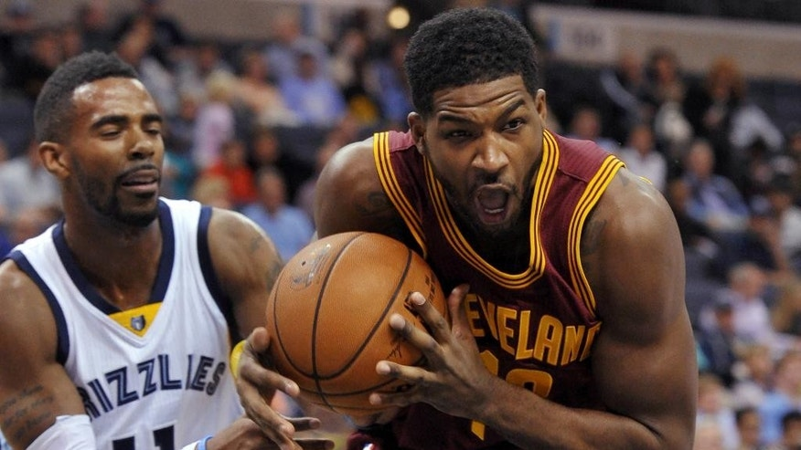 Cleveland Cavaliers forward Tristan Thompson, right, drives past Memphis Grizzlies guard Mike Conley (11) in the first half of a preseason NBA basketball game Wednesday, Oct. 22, 2014, in Memphis, Tenn. (AP Photo/Brandon Dill)