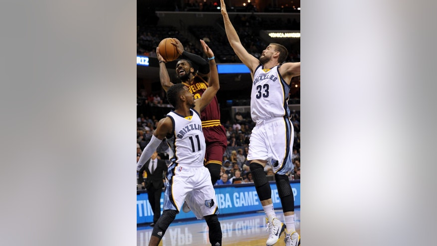 Cleveland Cavaliers guard Kyrie Irving (2) shoots against Memphis Grizzlies forward guard Mike Conley, left, and center Marc Gasol (33) during the first half of a preseason NBA basketball game Wednesday, Oct. 22, 2014, in Memphis, Tenn. (AP Photo/Brandon Dill)