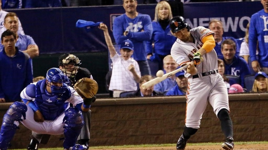 San Francisco Giants' Hunter Pence hits a two-run home run during the first inning of Game 1 of baseball's World Series against the Kansas City Royals Tuesday, Oct. 21, 2014, in Kansas City, Mo. (AP Photo/Charlie Riedel)