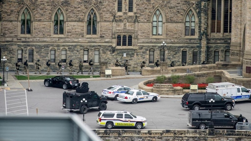 Police teams enter Centre Block at Parliament Hill in Ottawa on Wednesday Oct. 22, 2014.  A soldier standing guard at the National War Memorial was shot by an unknown gunman and people reported hearing gunfire inside the halls of Parliament. Prime Minister Stephen Harper was rushed away from Parliament Hill to an undisclosed location, according to officials. (AP Photo/The Canadian Press, Justin Tang)