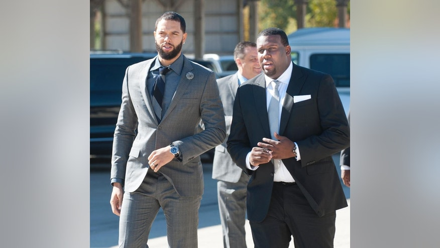 Brooklyn Nets basketball player Deron Williams, left, and Kansas asstistant coach Jerrance Howard arrive at a celebration of life ceremony for coach Wayne McClain in Champaign, Ill., on Wednesday Oct. 22, 2014. Both men played their college basketball at Illinois when McClain was an assistant coach. McClain died on Oct. 15. (AP Photo/The News-Gazette, John Dixon) MANDATORY CREDIT